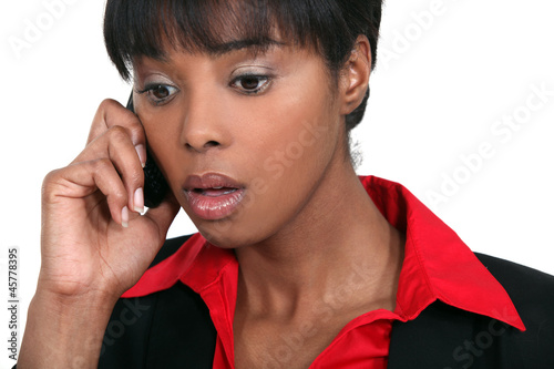 A black businesswoman getting bad news on the phone.