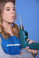 craftswoman pretending that her drill is a gun