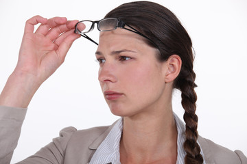 woman taking her glasses off to get a better look