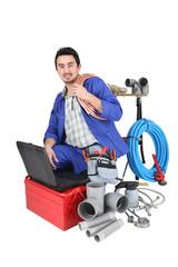 plumber kneeling with computer