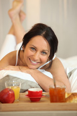 Brunette woman with breakfast in bed