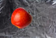 Red apple floating on a blurry silver background