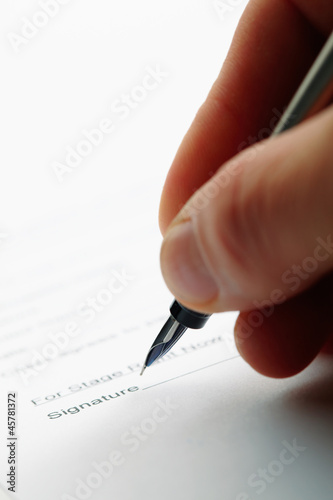 Closeup of a man holding a pen while doing document.