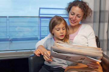 Mother daughter reading newspaper in cabin of passenger ship