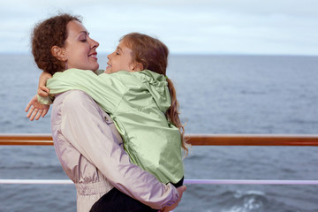 Mother daughter hugging on deck of large passenger ship