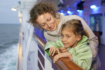 mother daughter in jackets posing on board passenger ship