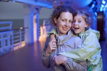 Mother daughter hugging smile on deck of passenger ship