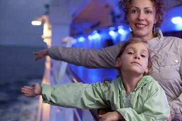 Mother daughter posing on board passenger ship