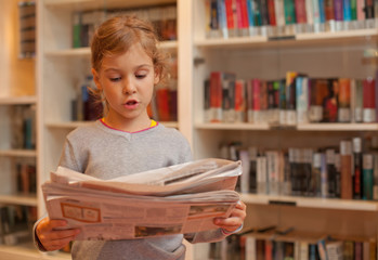 Little girl stands against bookshelves read newspaper