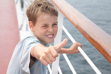 Little boy shows ok on deck of big passenger ship