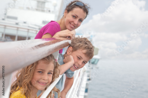 Mother with children stand on deck of passenger ship