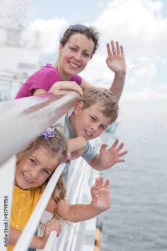 Mother with childrens stand on deck of ship and waving hands