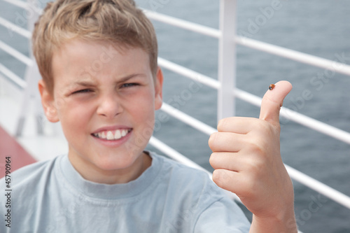 Ladybird on boy finger show ok on deck of ship