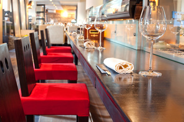 Red chairs near bar with glasses, towel in sushi restaurant