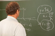 Scientist looking at formula on blackboard, back