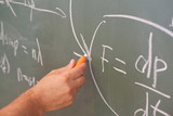Scientist write formula on blackboard, focus on hand