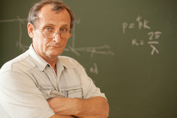 Scientist pose on background of blackboard