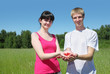 Wife, husband hold berry in hands in field