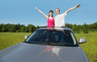 Husband, wife pose in hatch of car before hood in field