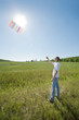 young man launch kite in field