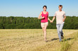 Husband, wife holding hands run in field near wood