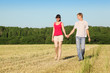 Husband, wife holding hands walk in field near wood