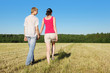 Husband, wife holding hands walking in beautiful field, back