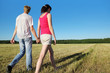 Happy husband, wife hold walk in field near wood, side