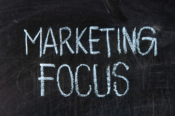 MARKETING FOCUS handwritten with chalk  on a blackboard