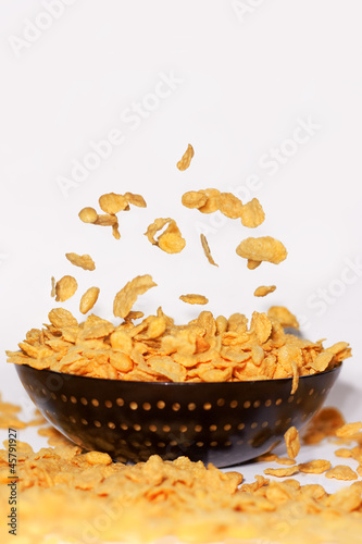 Golden cornflakes falling into black bowl - isolated on white