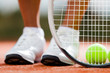 Legs of sportive girl near the tennis racquet and balls