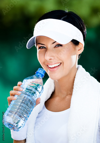 Sporty woman with plastic bottle of water after tennis training