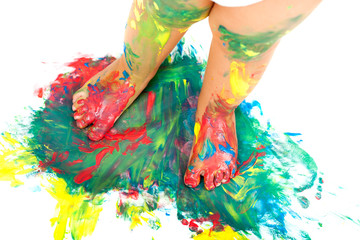Babies feet on colorful mosaic paint.