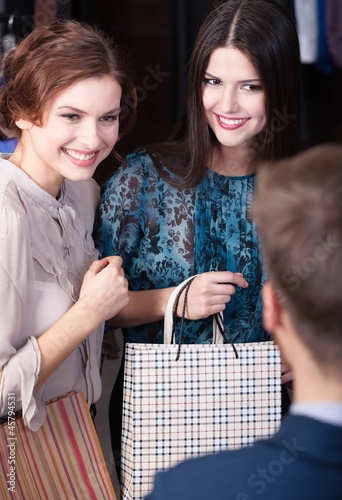 Shop assistant gives a piece of advice to beautiful clients