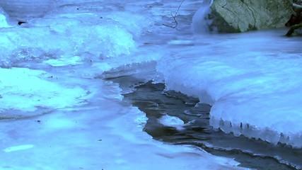 Unter der Eisschicht fliesst das Wasser des Bachs