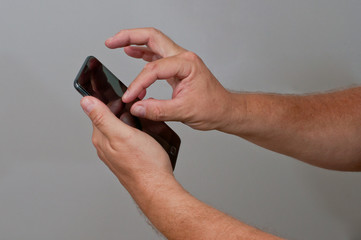 A man taps on mobil phone with fingers