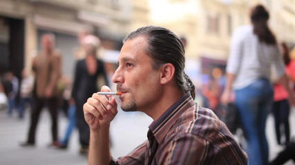 depresed man smoking on the street
