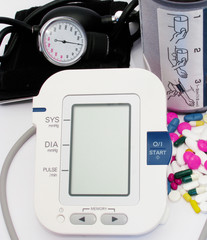 Blood pressure device and pills isolated on white background
