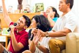 Asian people singing at karaoke party