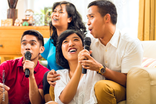 Asian people singing at karaoke party and having fun