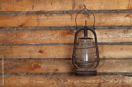 The old kerosene lamp hanging on the wall of a wooden house
