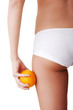 Girl holding an orange next to the buttocks is isolated