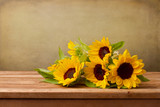 Sunflowers on wooden table against grunge background