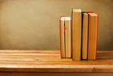 Vintage old books on wooden deck tabletop against grunge wall poster