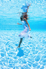 Underwater woman with white dress in swimming pool