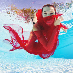 Underwater woman with red veil in swimming pool