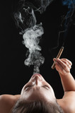 Woman smoking cigar against dark background. Fashion photo