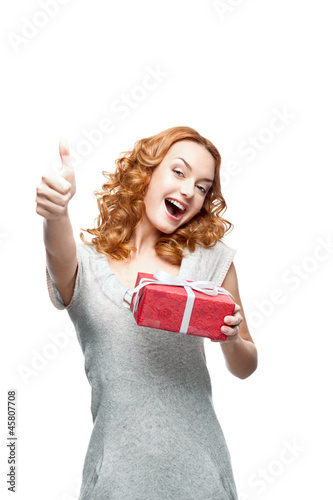 young red-haired casual girl with red gift showing thumb-up