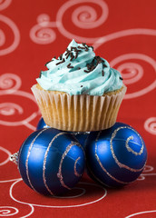 One blue cupcake and two christmas balls 2
