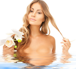 beautiful woman with orchid flower in water